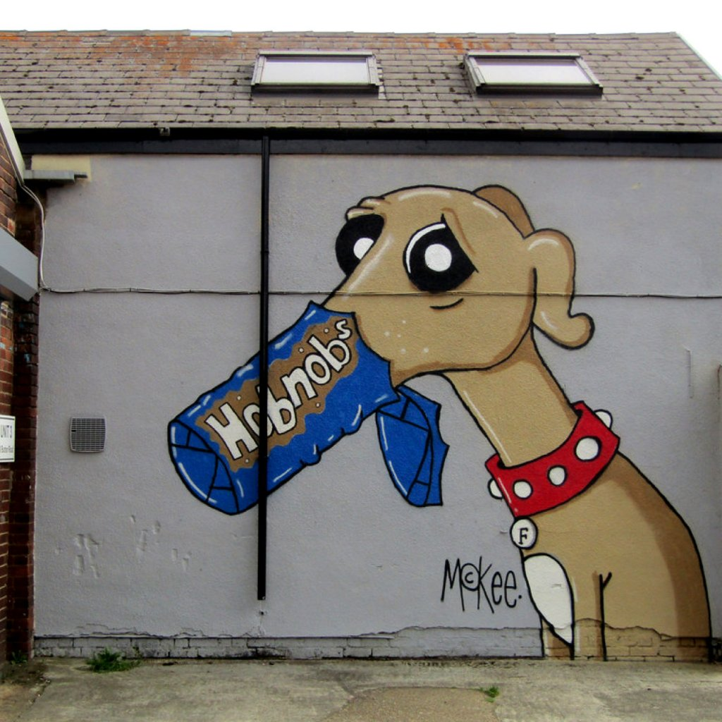 Dog with it's mouth in a Hobnob's packet, painted on the side of a building in Kelham Island by Pete McKee