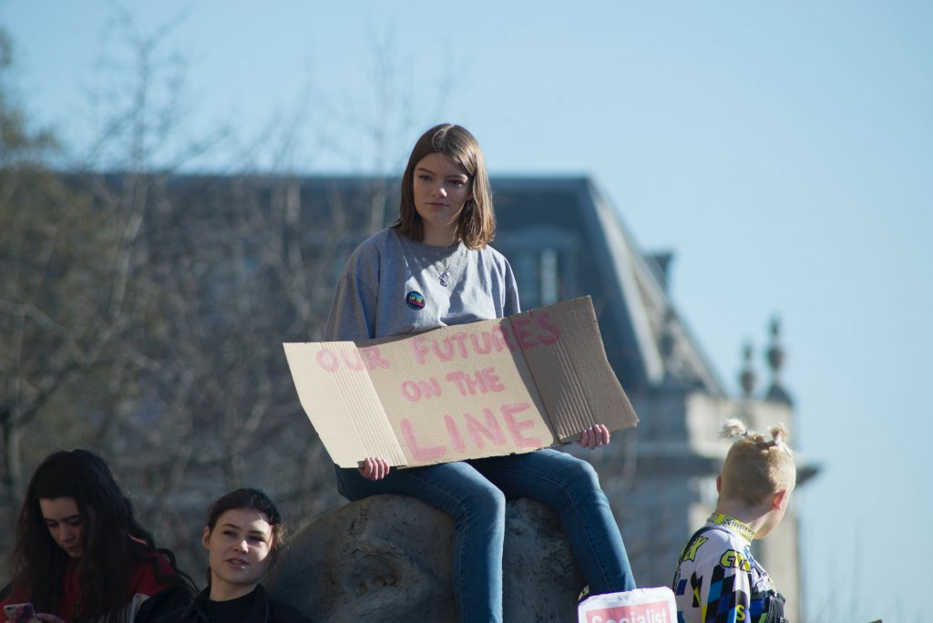"A young girl with a sign that reads ""OUR FUTURES ARE ON THE LINE"""